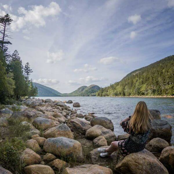 Woman sitting on a rocky lake shore overlooking Jordan Pond at Acadia National Park