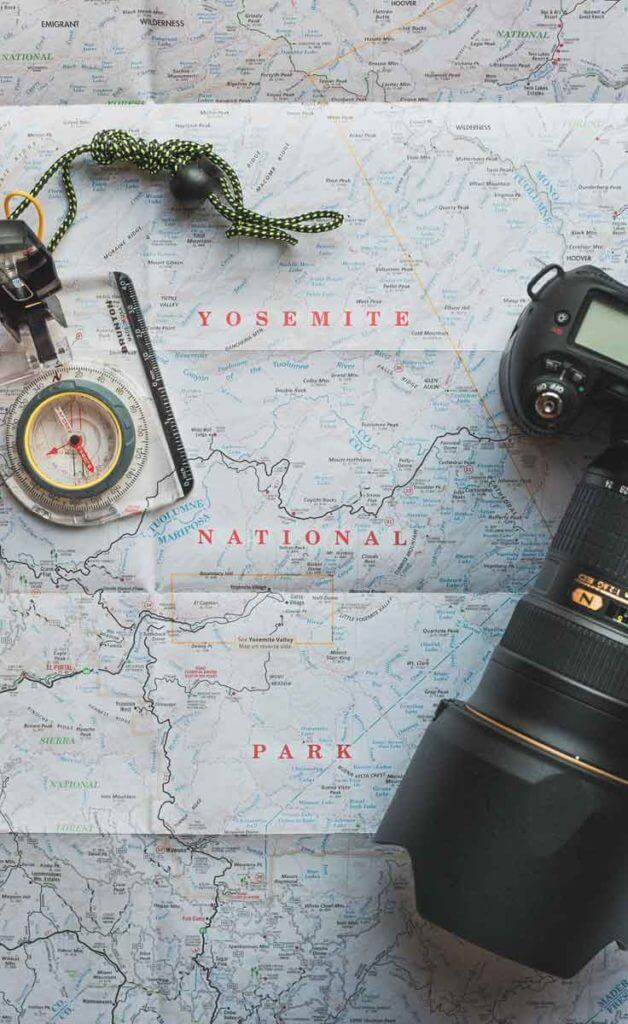 Flat lay photograph of a map of Yosemite National Park with a compass necklace and a dSLR camera with a long lens on top.