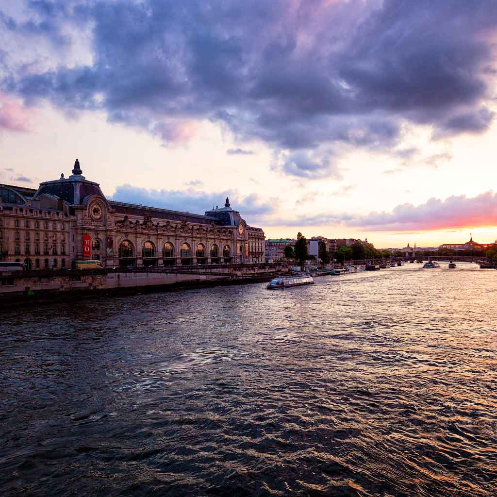 Landscape view of the Seine River in Paris during sunset with Musée d'Orsay in the background.
