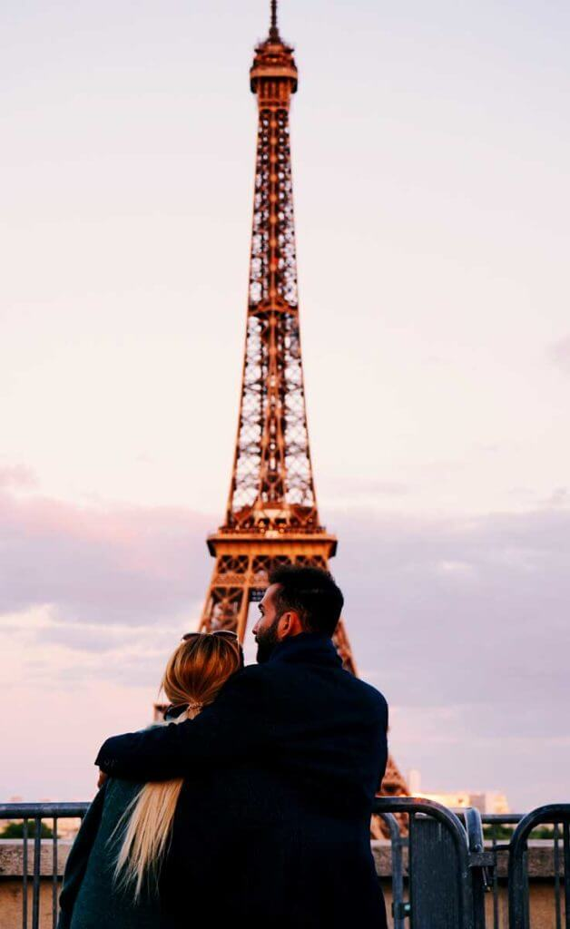 A man with his arm around the shoulders of a woman stand at a railing looking out toward the Eiffel Tower in Paris, France.