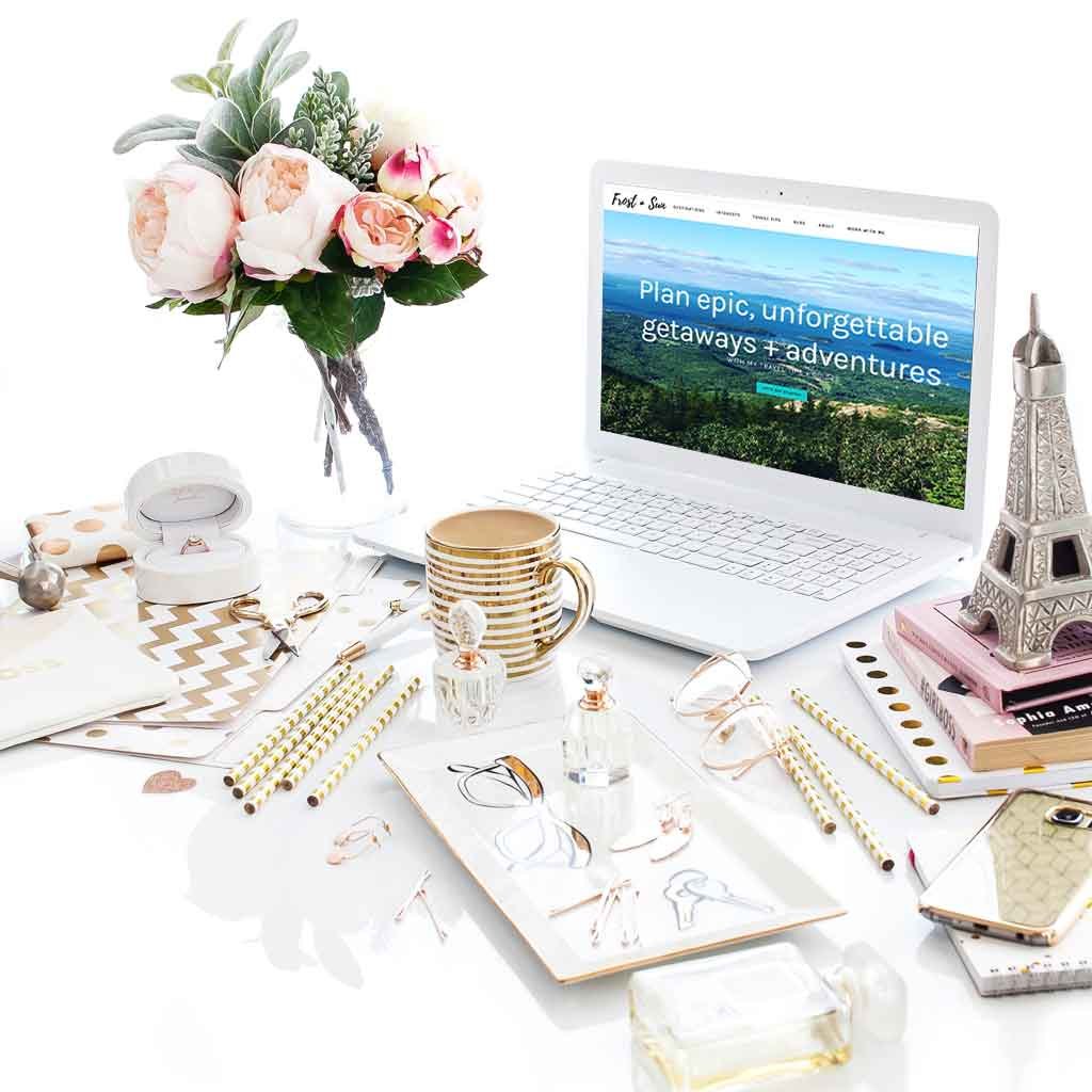 Landscape view of a white desk with lots of gold and pink accessories, including an Eiffel Tower replica, and a laptop open to Frost + Sun website.