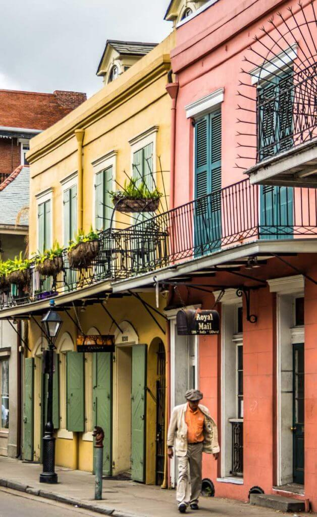 Photo of yellow and coral buildings in New Orleans' colorful French Quarter neighborhood, with an older gentleman in a tan suit and orange shirt walking by.