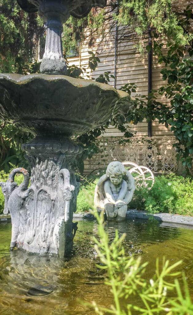 Closeup of a water fountain outside the Cornstalk Hotel, with a sullen cherub statue in the background.