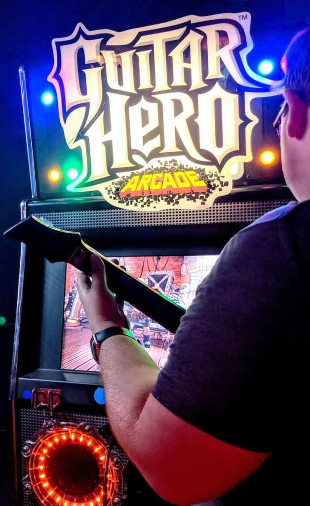 Closeup of a man playing Guitar Hero at an arcade.