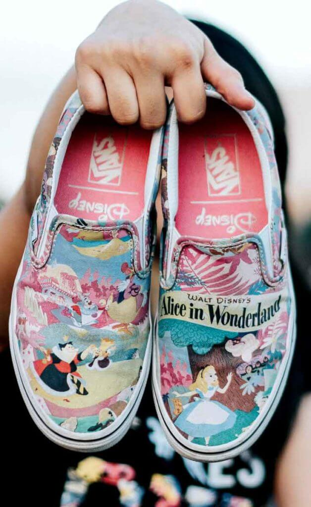 Photograph of a woman holding up a pair of Vans classic slip-on sneakers with a bright Alice in Wonderland themed print.