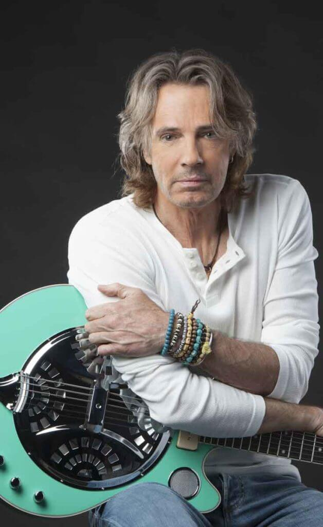 Photograph of musician Rick Springfield wearing a white long sleeve henley tee and jeans, leaning over an aqua guitar.