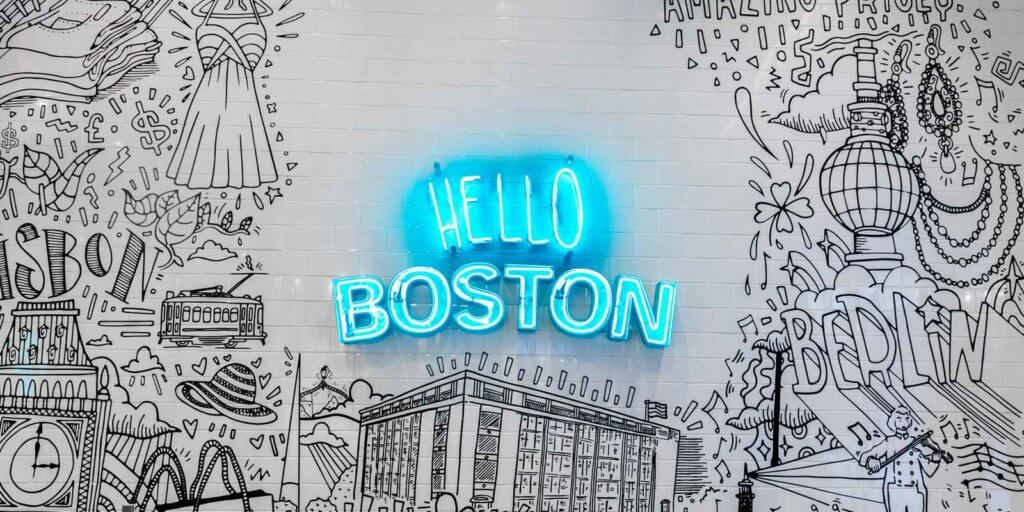 "Black and white drawing on subway tile with a blue neon sign in the middle that reads ""Hello Boston."""