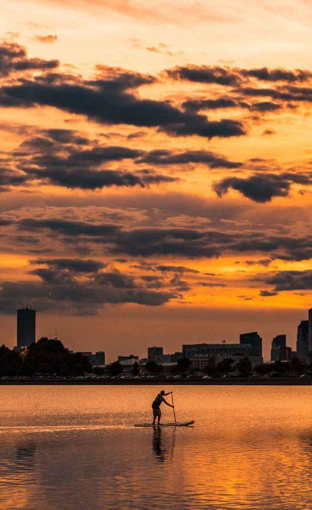 Man paddleboarding in the ocean nearby Castle Island in South Boston