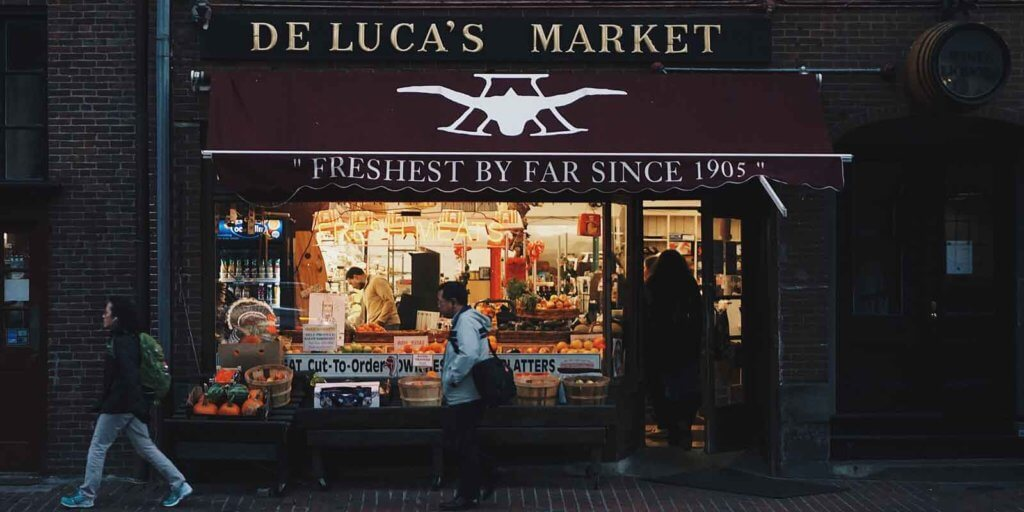 Landscape photo of the storefront for De Luca's Market on Newbury Street in Boston, MA, USA.