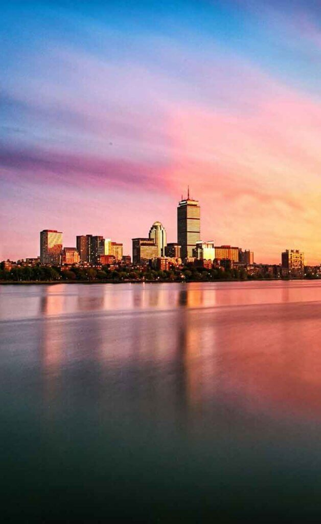 Boston city skyline showing the Prudential Center across the Charles River with cotton candy colored skies during the sunset.