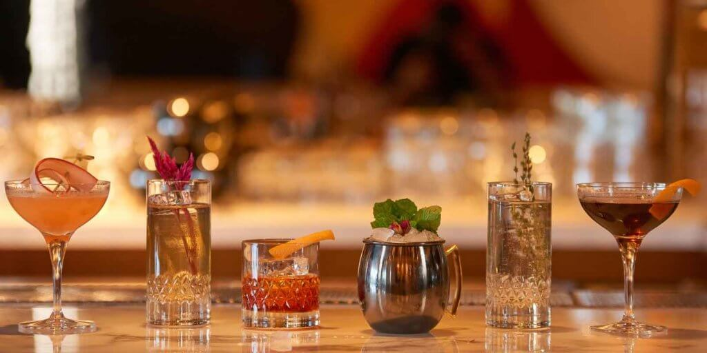 Closeup of a bar featuring 6 cocktails, all with botanical sprigs or other fun garnishes.