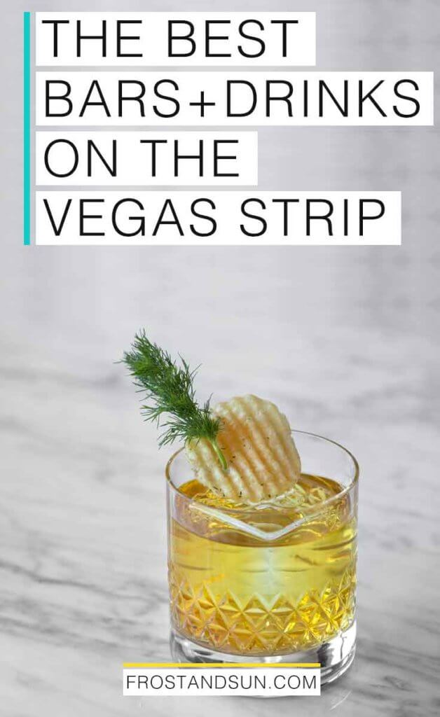 """Closeup of a yellow tinted cocktail garnished with a potato chip and sprig of dill on top of a grey and white marble counter. Overlying text reads """"The Best Bars + Drinks on the Vegas Strip."""""""