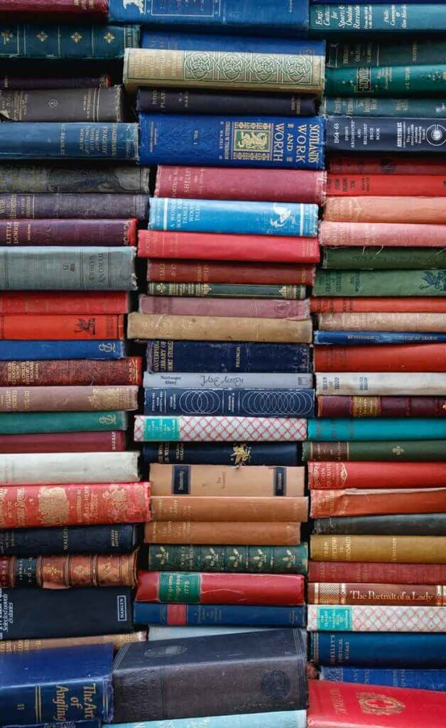 Close up of vertical stacks of vintage books in a variety of colors like red, navy blue, forest green, tan, and more.