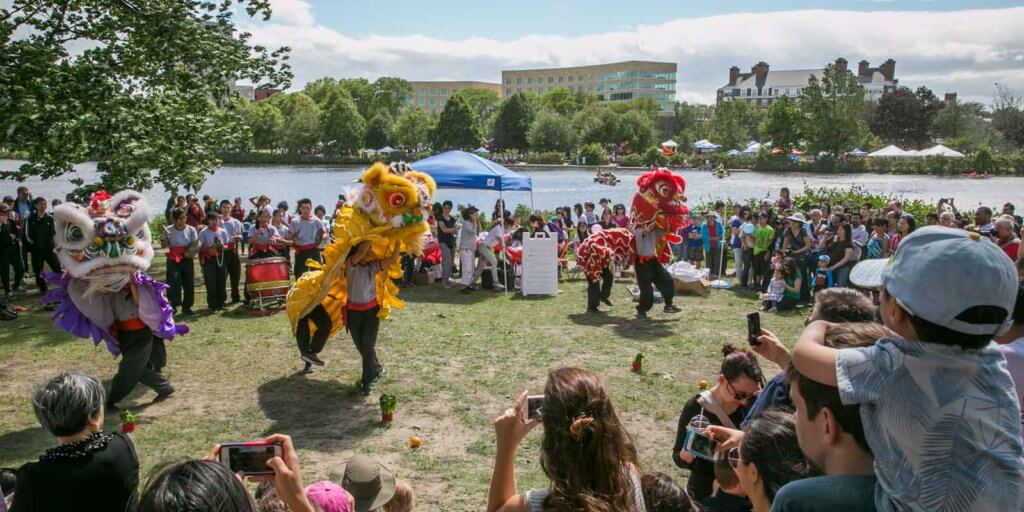 Landscape photo of a Chinese dance performance with colorful dragon costumes at the Boston Dragon Boat Festival.