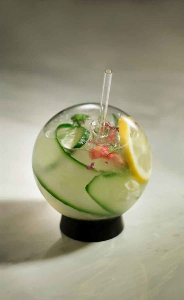 Closeup of a spherical glass filled with a gin cocktail, long strips of cucumber, lemon slices, and a flower garnish.