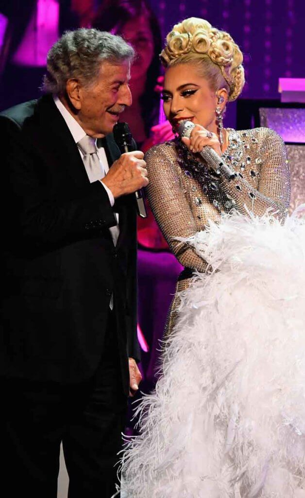 Singers Tony Bennett, in a black suit, and Lady Gaga, in a silver sparkly and feather adorned gown, sing on stage at the MGM Park Theater.