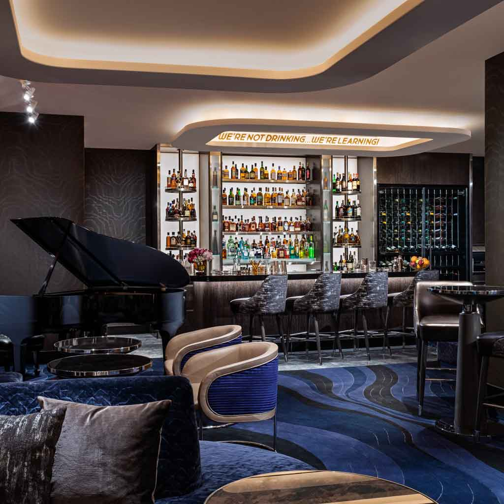"""Photograph of Mr. COCO lounge and restaurant, with dark grey and cobalt blue decor, a Steinway piano, and a bar filled with prime liquor. A sign says """"We're not drinking...we're learning!"""""""