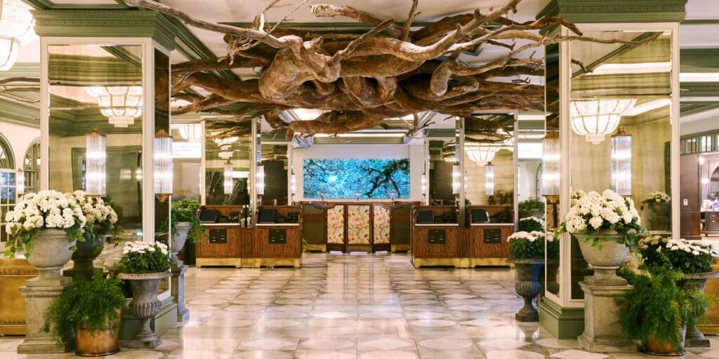 Landscape view of the hotel lobby at Park MGM with plants, white potted flowers, and a ceiling sculpture that resembles tree roots.