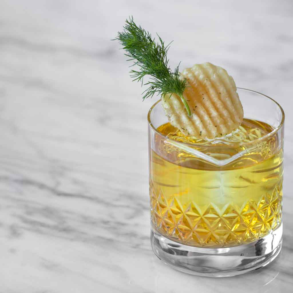 Closeup of a short glass with a yellow tinted cocktail garnished with a rippled potato chip and sprig of dill.
