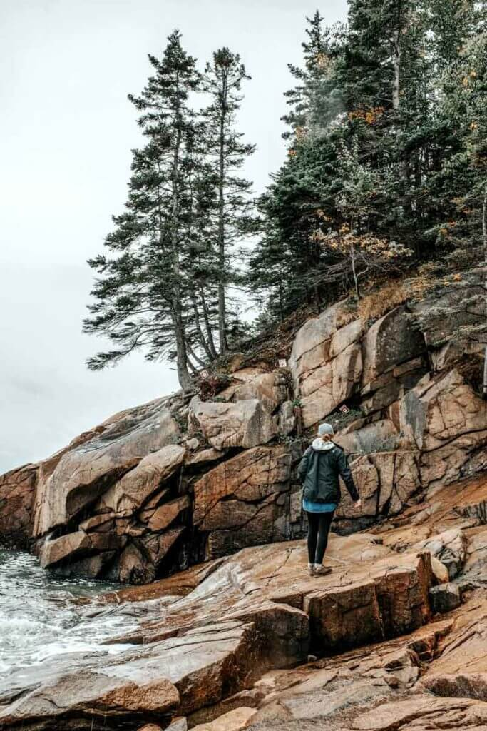 A woman walking up a rocky cliff at Acadia National Park in Maine.