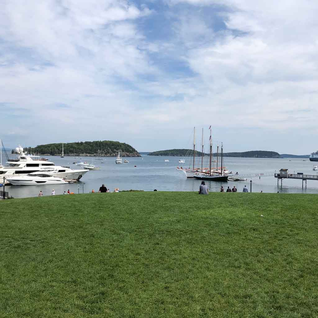 Landscape view of Agamont Park, near the start of the Bar Harbor Shore Path, with a pier, yachts, and sailboats in the distance.