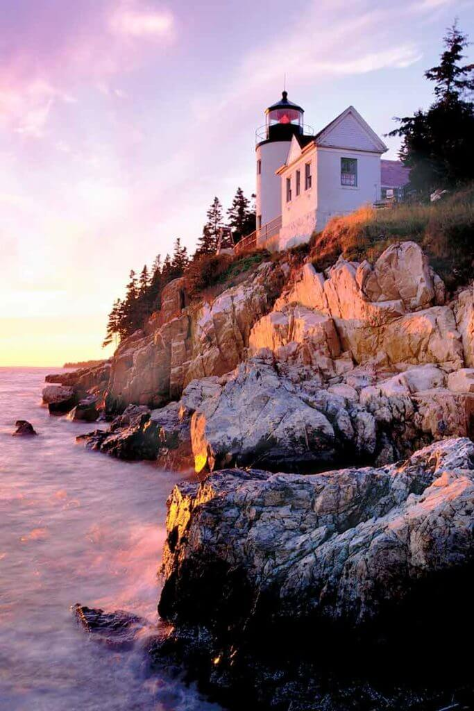Photograph of the Bass Harbor Head Lighthouse on a rocky cliff during sunset.