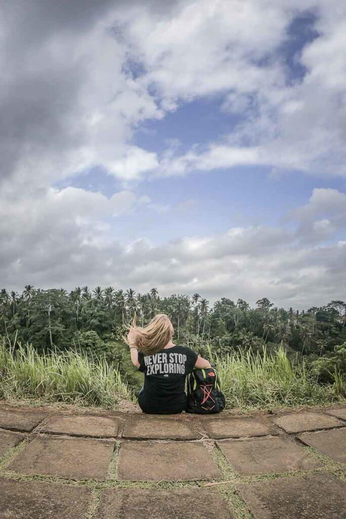 Adventure travel blogger overlooking a tropical forest from a ridge.