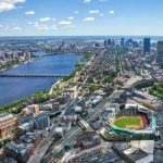 Aerial view of Boston, MA with the Major League Baseball Boston Red Sox's Fenway Park in the foreground. Boston sports tickets can be pricey, but discounts are available for those on a budget!