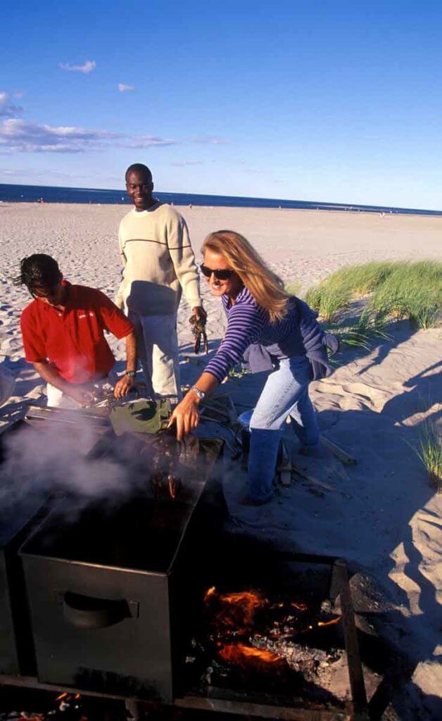 People setting up a clambake on Crane Beach in Ipswich, MA.