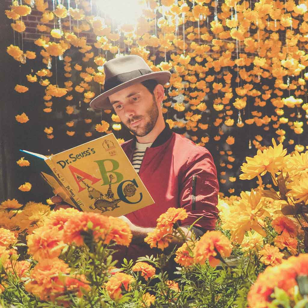 A man reading Dr Seuss's ABC book amongst lots of yellow and orange flowers.