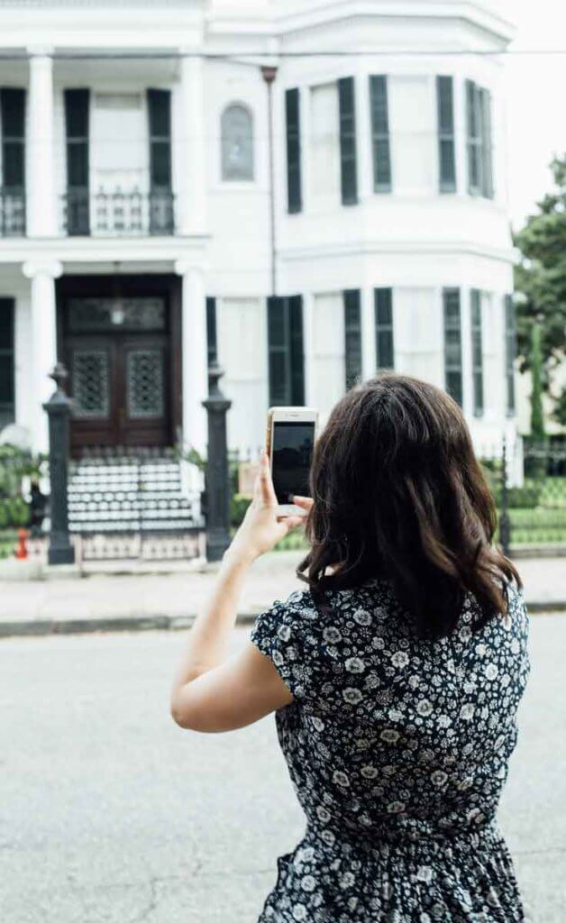 Woman taking a photo of a mansion on a smartphone.