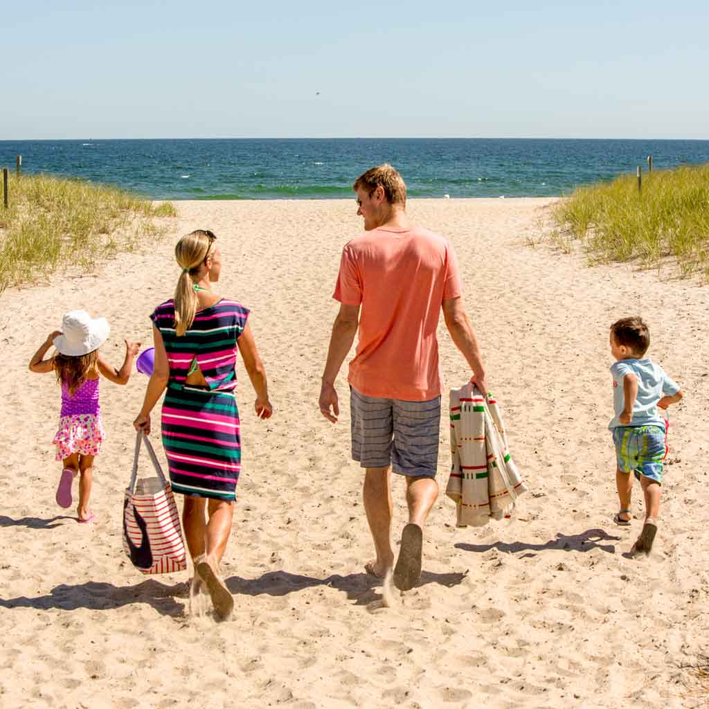 Photo of a family with 2 children walking toward the ocean at Hampton Beach, NH, one of many fun beaches available on a day trip from Boston.
