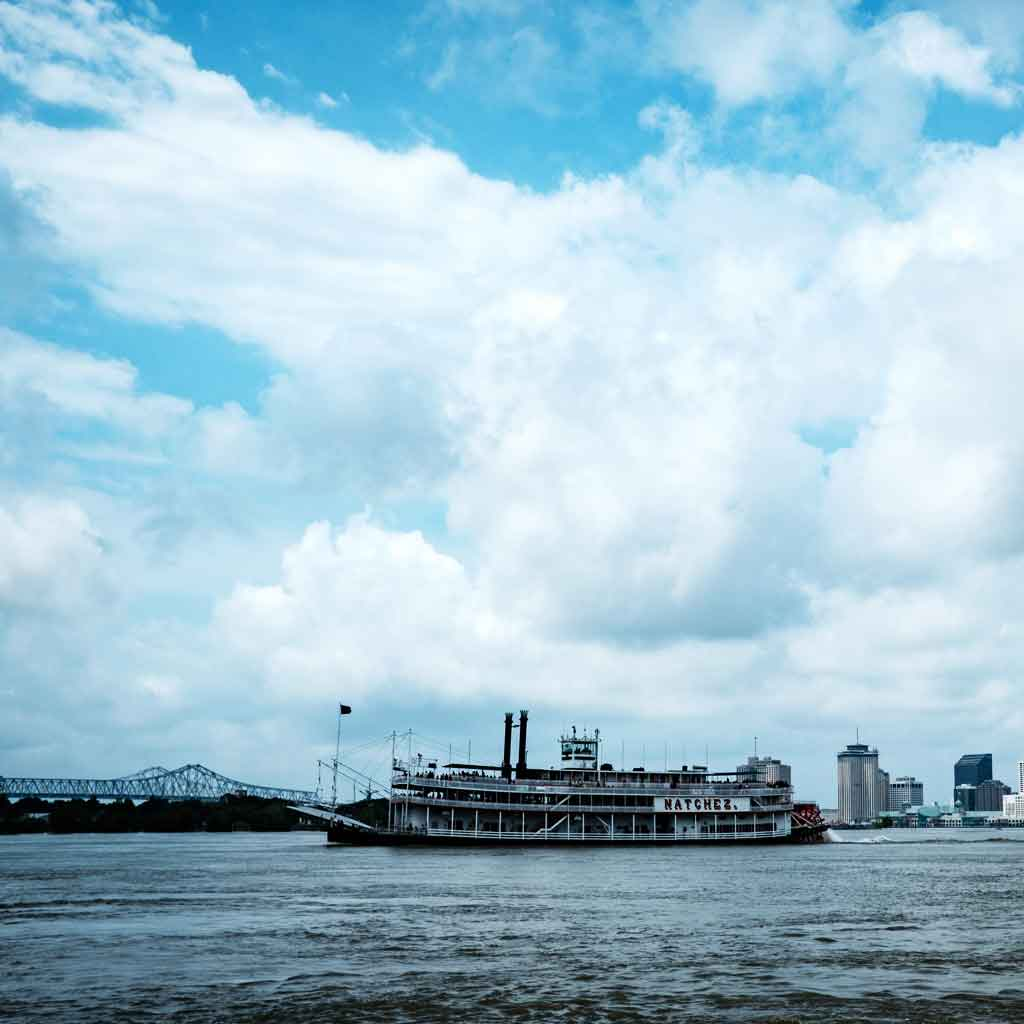 "Photograph of blue, yet cloudy, skies with a steamboat floating by with a sign that says ""Natchez."""
