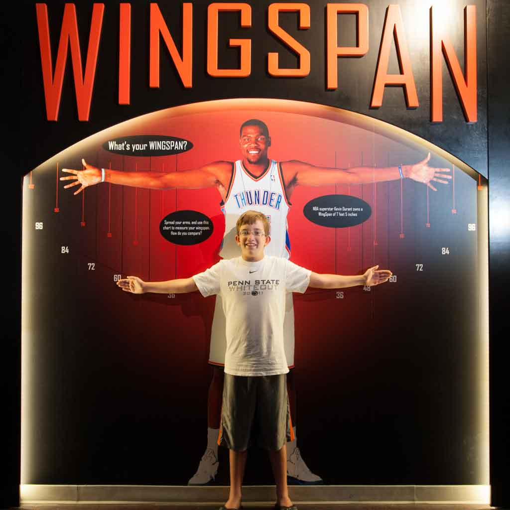 A young boy measures his wingspan against a basketball player at the Naismith Memorial Basketball Hall of Fame in Springfield, MA.