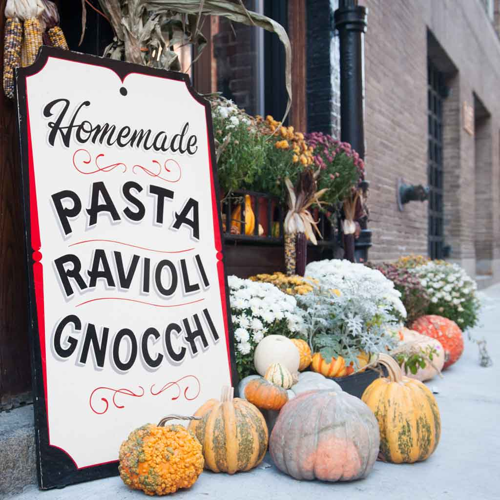 "Closeup of a sign that reads ""Homemade Pasta Ravioloi Gnocchi"" with mums, gourds, and pumpkins surrounding it."