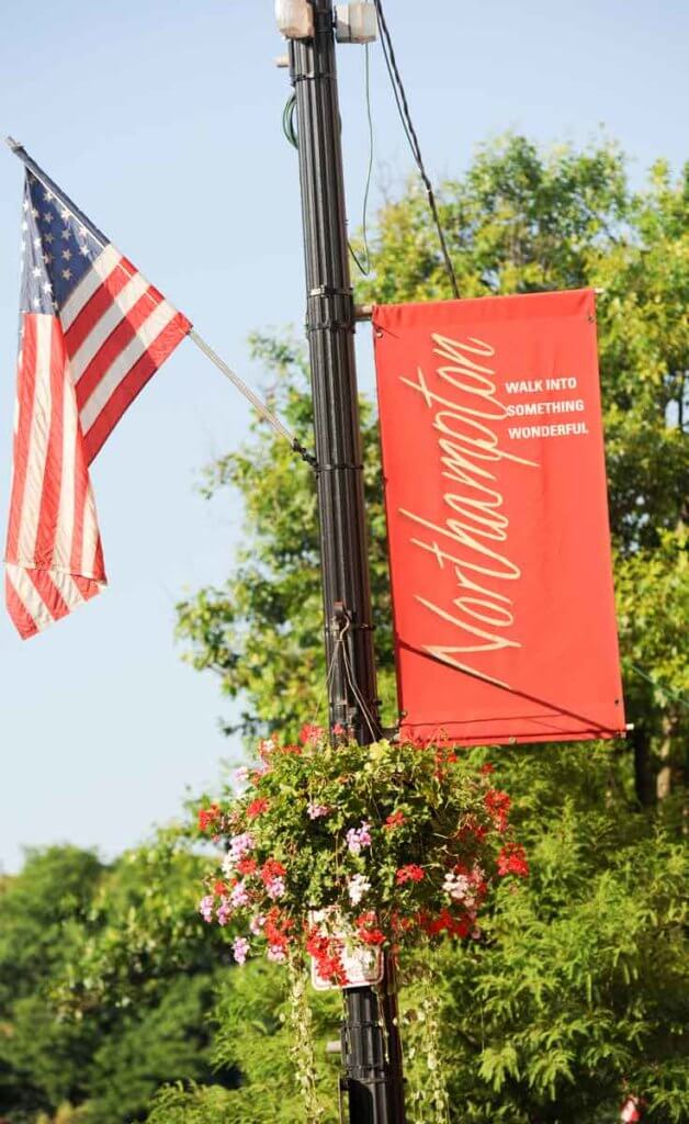 "Closeup of a light pole in Northampton, MA with a flower basket, American flag, and a red flag with ""Northampton: Walk into something wonderful"" written on it."