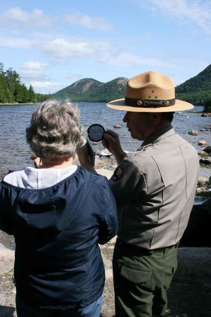 A man in a uniform shows a camera filter to a woman while overlooking the Bubble Mountains in Bar Harbor, Maine.