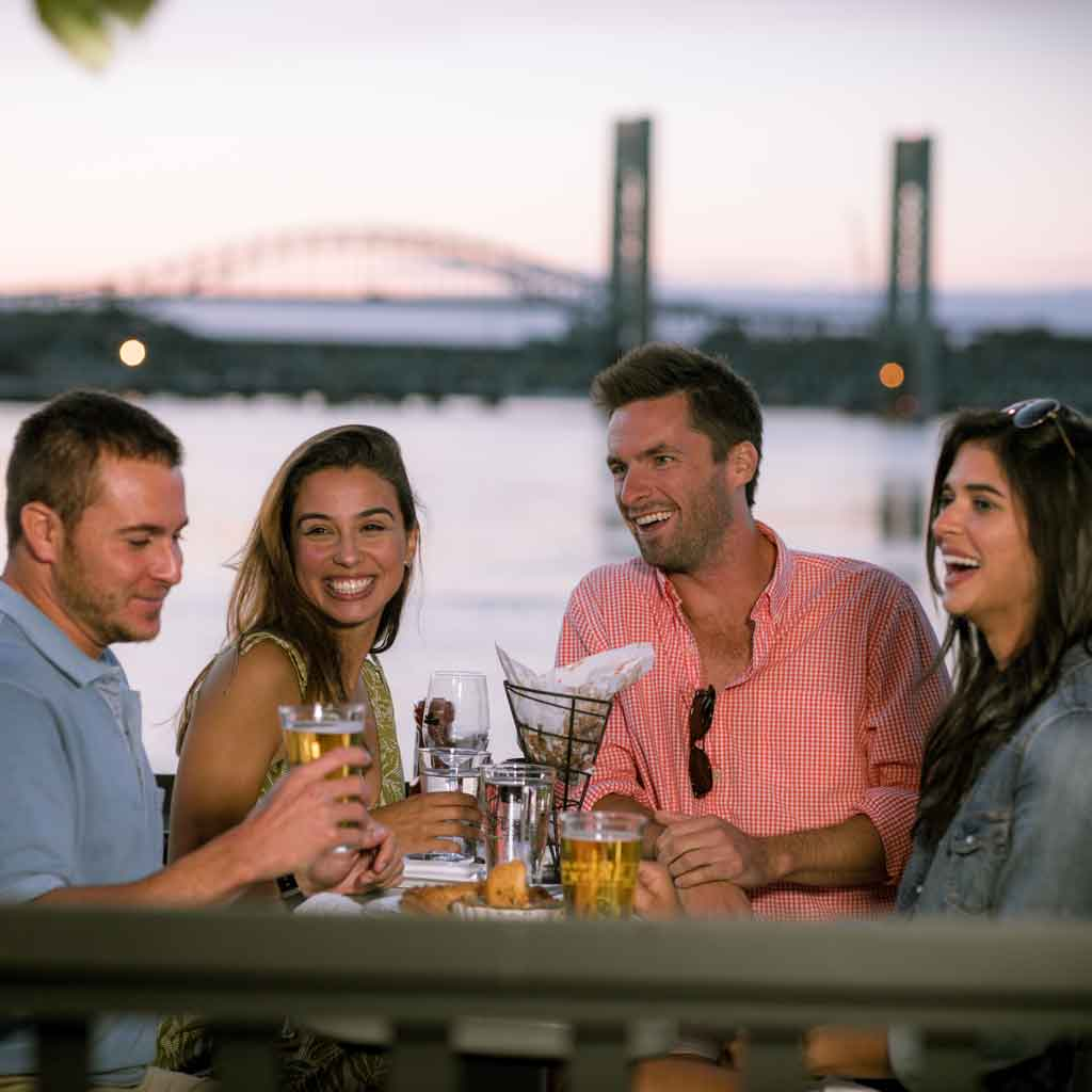 A group of 4 adults sitting at an outdoor table at a restaurant with beer and food in Portsmouth, NH. Portsmouth is an up-and-coming foodie hotspot perfect for culinary day trips from Boston.