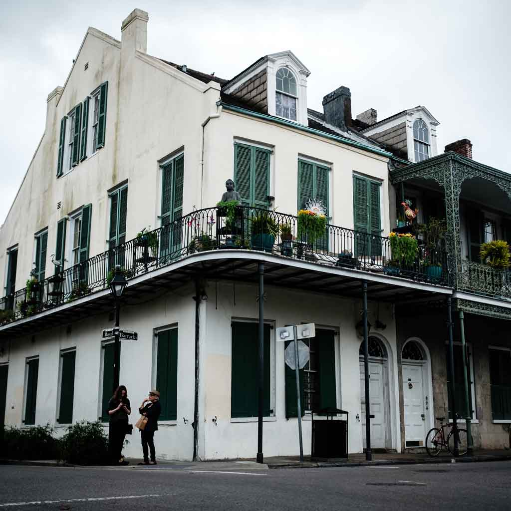Close up of an old white house with green shutters and a decorative iron balcony; 2 women stand below on the sidewalk.