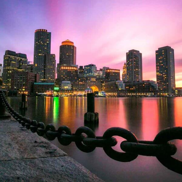 Landscape view of the Boston waterfront during sunrise with blue, purple, pink, yellow and orange skies with the cityscape in the background.