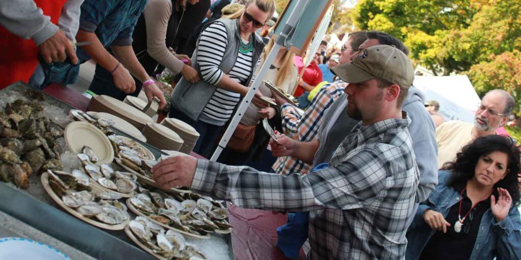 Crowds surrounding a table full of wellfleet oysters at the Wellfleet OysterFest.