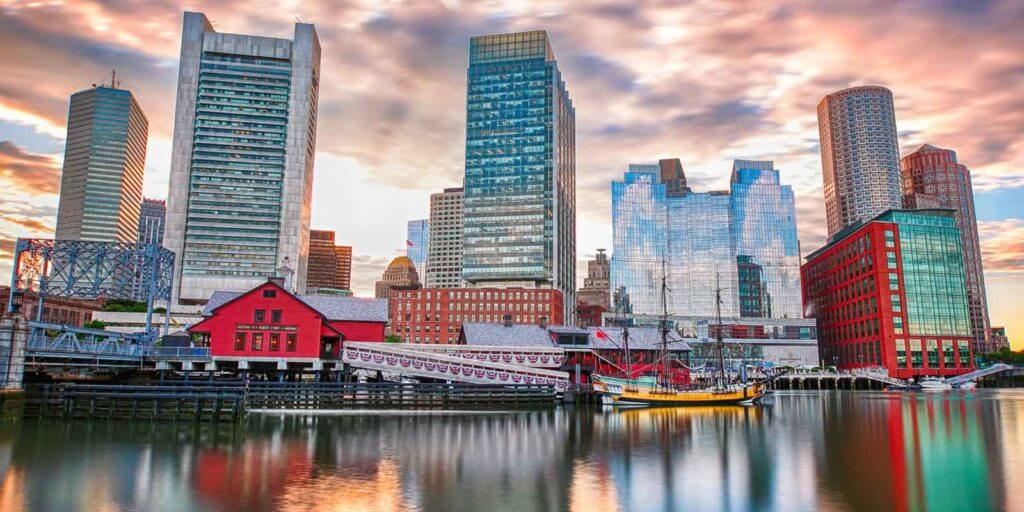 A view of one of Boston's waterfront neighborhoods with buildings reflecting on the water.