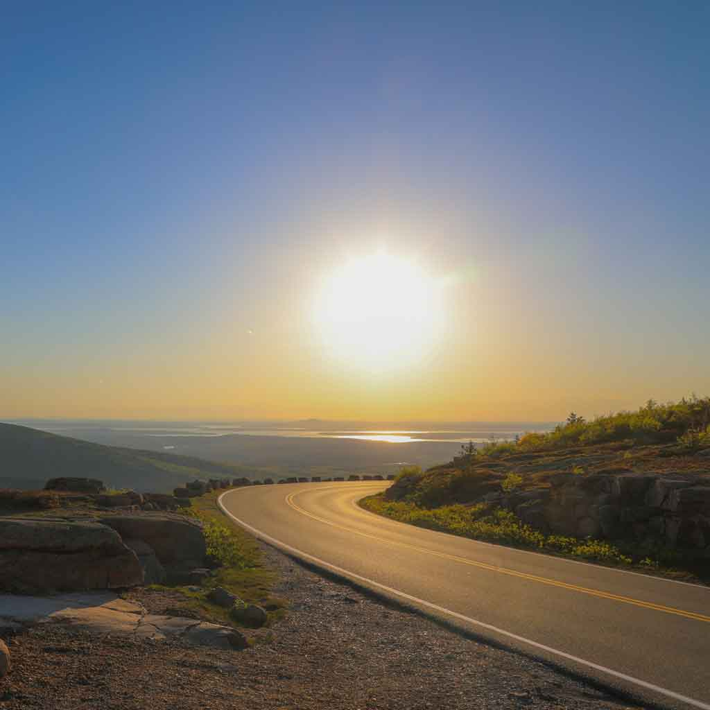 Photo of a bright sunrise over a curved road looking out over a valley.