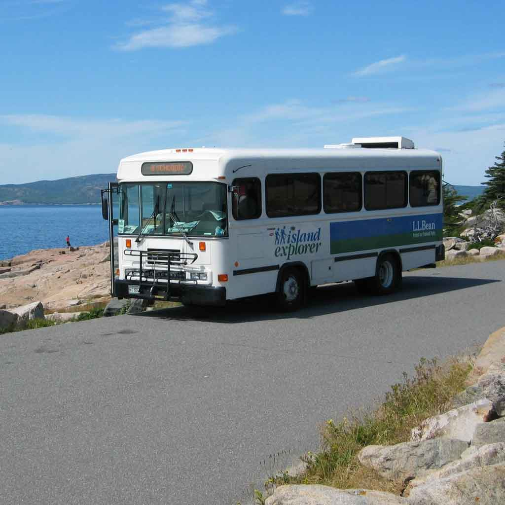 "Photo of a bus pulled over on the side of a road. Writing on the bus reads ""Island Explorer."""