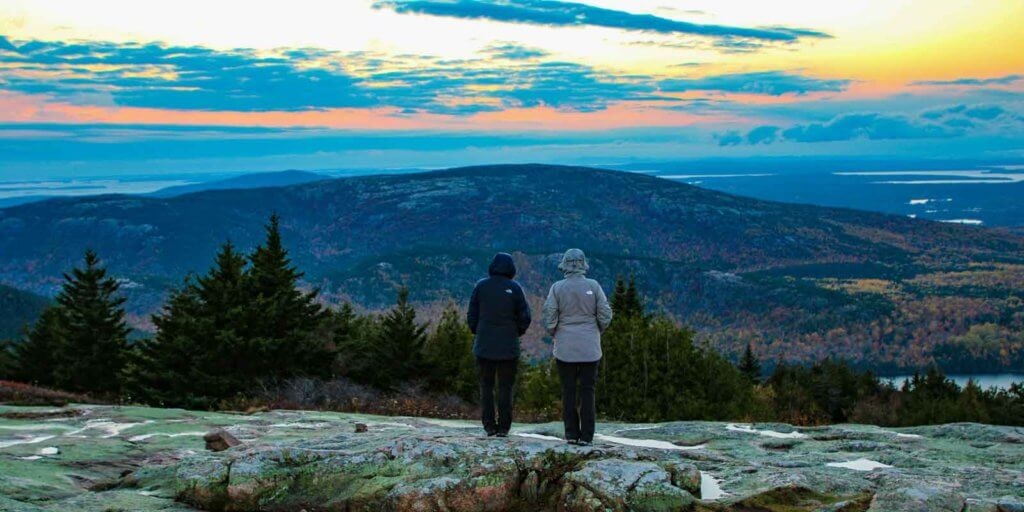 Two people in hooded jackets watching the sunset from Cadillac Mountain.