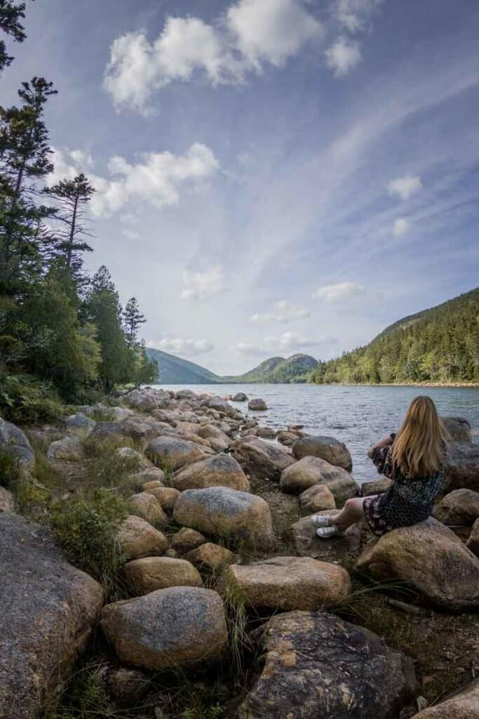 Woman sitting amongst rocks along the shoreline of Jordan Pond hiking trail.
