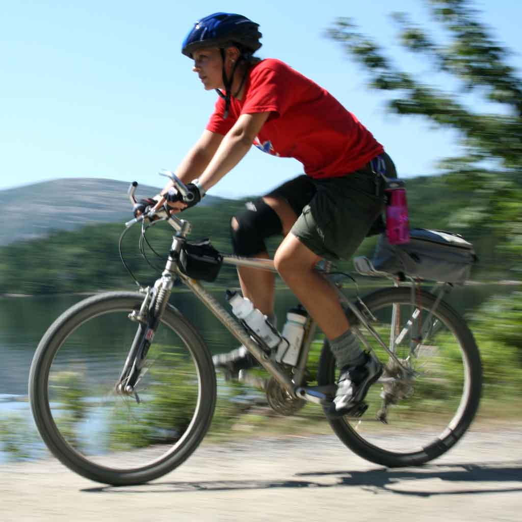 Person wearing a helmet, riding by on a mountain bike