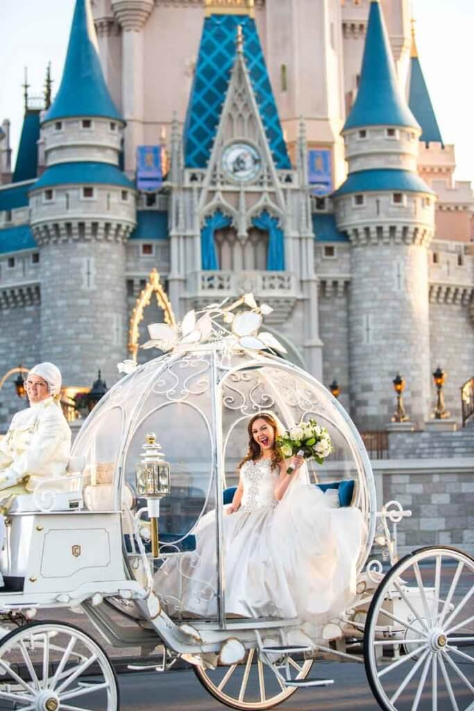 Bride sitting in a pumpkin shaped coach in front of a castle.