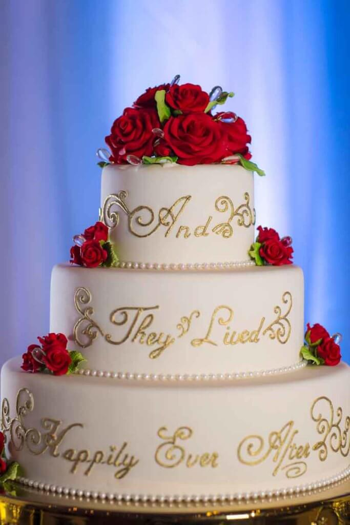 "Closeup of a white and gold wedding cake covered in red roses. Text on the cake reads ""And they lived happily ever after."""