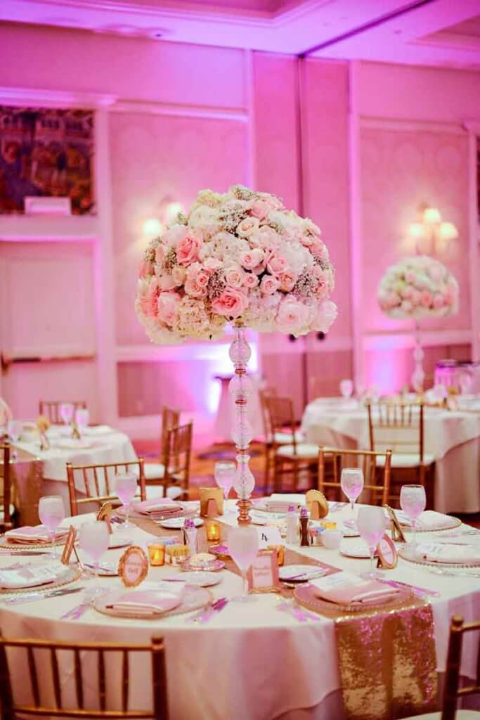 Photo of a table with a fancy setting for a wedding with a tall crystal vase filled with white and pink flowers.